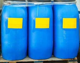 Scratched blue packed barrels with yellow labels