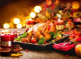 Thanksgiving dinner table served with turkey, decorated with bright autumn leaves