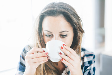 A young woman sitting at a table in a bar indoors drinking from a ceramic mug. Face Close-Up