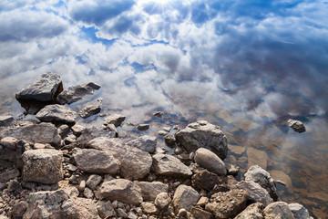 Still lake coast, coastal stones and blue cloudy sky