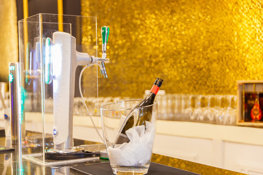 Carafe, bottle and dispenser with beer and ice on the table.