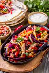 Pork fajitas with onions and colored pepper, served with tortillas.