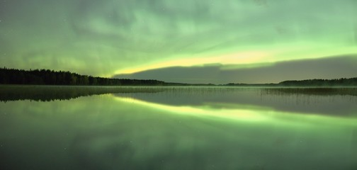 Northern lights (Aurora Borealis) in the night sky over a beautiful lake in Finland. Vibrant green colors on the sky and symmetric reflections on the still water of the lake. Panorama image.