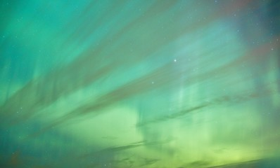 Vibrant colors of the northern lights (Aurora Borealis) dancing in the night sky in Finland. Abstract nature background with green tones.