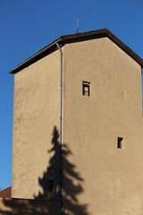 Ein Turm mit einem Schattenbild eines Baumes