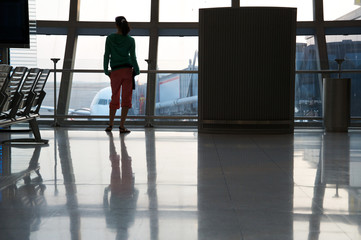 Woman looking through the window in the airport
