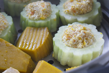 pumpkin and bitter melon stuffed with vermicelli, tofu, corn and carrot while steaming in steaming pot (vegetarian food)