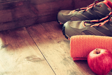 fitness concept with towel, apple and sport footwear over wooden background. retro filtered