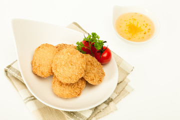 Fried coated cutlets with cherry tomatoes in a bowl