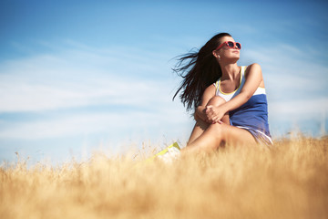 Freedom concept. Beautiful woman enjoying summer sun in the fiel