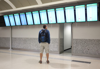 Man is looking and pointing at a departure/arrival board at an airport