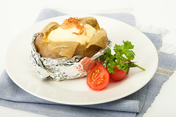 Baked potato with cheese in foliage with fresh tomato