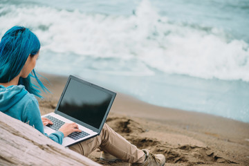 Freelancer girl working on laptop on coast