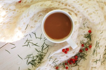 Comfy time with cup of hot coffee drink in winter morning at home. White mug and white knitted wool blanked on wooden table,decorated fir needles and red berries. Soft focus, shallow dof.
