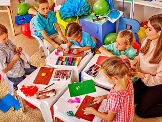 Kids holding colored paper and glue on table in kindergarten .