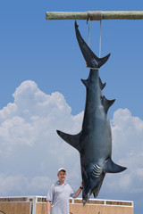 Fisherman posing with his catch of a giant mako shark that is hanging from a pole.