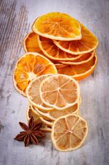 Keuken foto achterwand Plakjes fruit Slices of dried lemon, orange and star anise on old wooden background