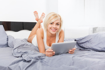 beautiful woman lying on bed using digital tablet