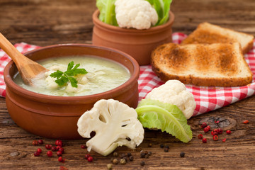 Cauliflower soup in clay bowl with toasted bread