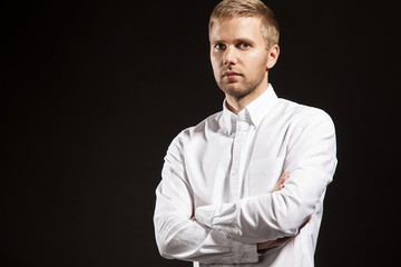 Confident man in a white shirt on a black background