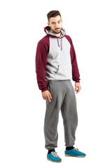 Serious confident young man in casual sportswear looking at camera. Full body length portrait isolated over white studio background.