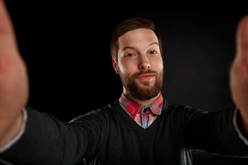 Life style concept. Young man with a beard  in shirt and pullover holding mobile phone and making photo of himself while standing against black background.
