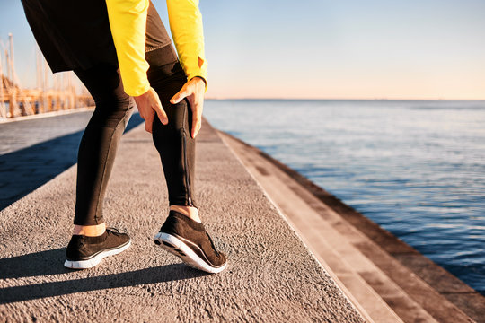Muscle injury - Athlete running clutching calf muscle after spraining it while out jogging on the beach near ocean. Sports injury concept with running man outside.
