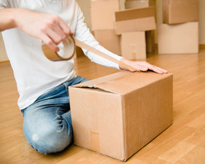 Close up of person hands packing cardboard box