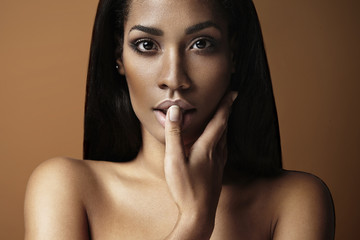 black woman touching her lips with a finger