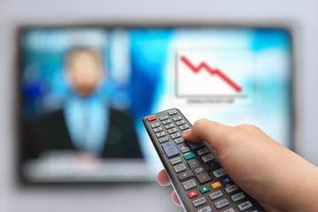Man hand switches TV channels. Remote control in hand and TV. News in prime-time