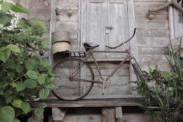 Old bicycle standing near a wood wall.
