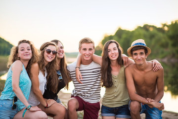 trendy teenagers on the beach at sunset, holidays, friendship