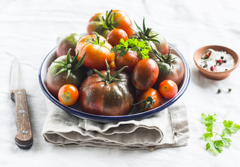 fresh tomatoes on a white enamel plate on a light surface