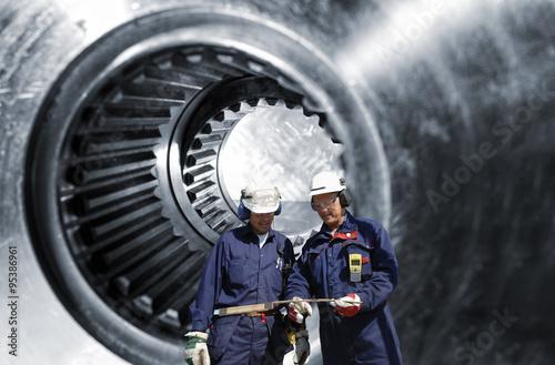 Wall mural steel workers, engineers with large cogwheels,  gear axle in background