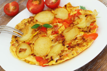 Omelette with potatoes, onions, red pepper and sweetcorn on white plate, closeup