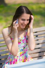 A girl wearing color dress used cell phone in summer park
