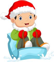 Kids wearing a santa hat sliding on snow