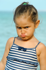 Little girl with glower on the beach. Little girl frown on the beach. Little girl tantrum.