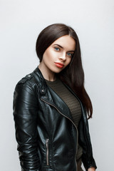 Portrait of a beautiful woman in a black leather jacket and knitted sweater
