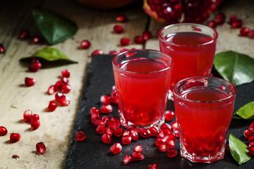 Fresh pomegranate juice on a black background, selective focus
