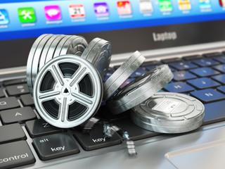 Video or movie online internet concept. Film reels on laptop key