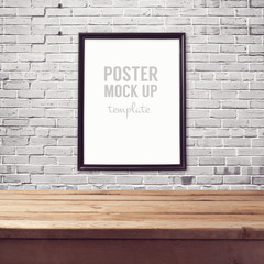 Poster mock up template with wooden table over brick white wall