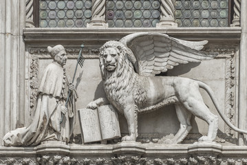 Sculpture of winged  lion of Venice with priest and book, Venice