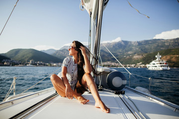 long hair girl in fashion jeans shirts on yacht in Montenegro
