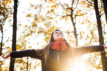 young happy woman with cheering hands in park. Female enjoying autumn sun