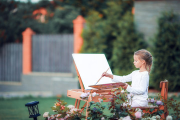 Adorable little girl painting a picture on an easel on a warm day outdoors