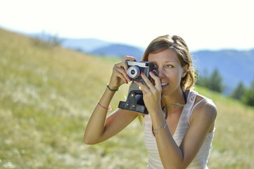 Young and  beautiful woman holding a retro camera