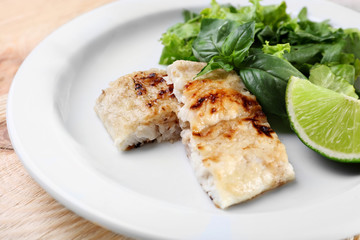 Dish of fish fillet with greens and lime on table close up