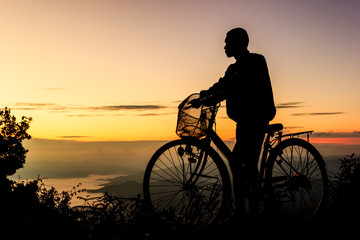 Boy riding bicycle on sunrise background.Silhouette