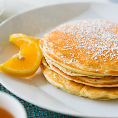 Pancakes with sugar powder on white plate